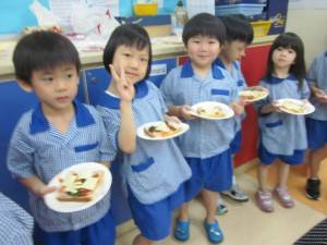 K2 children queuing to bake their spinach pizzas